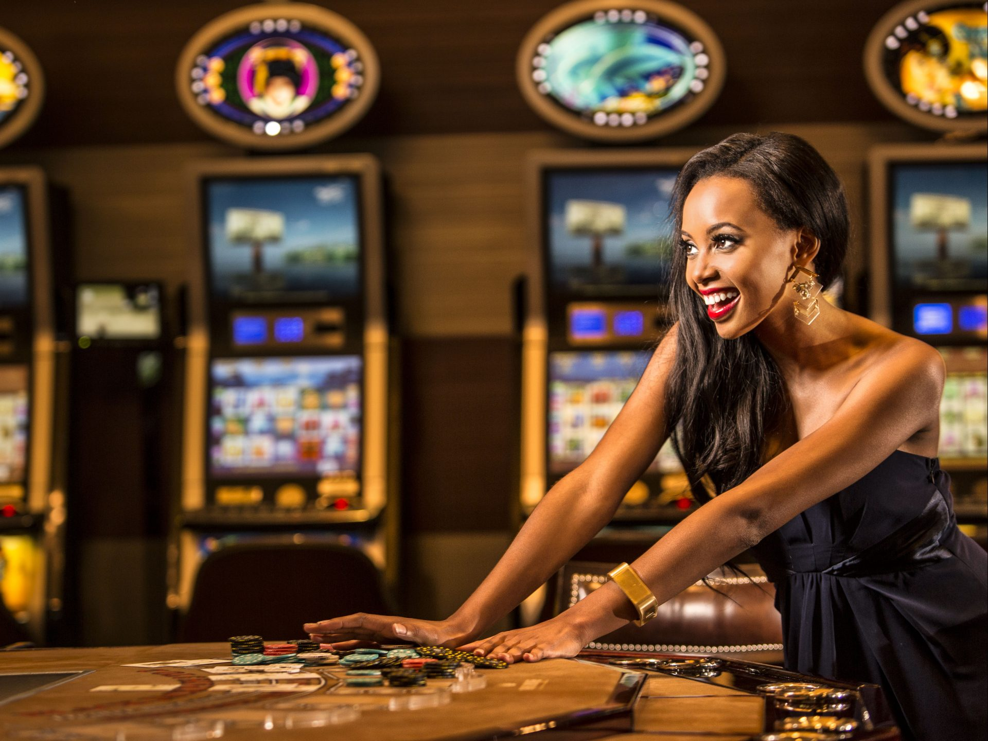Lady winning at casino table games with slot machines behind her