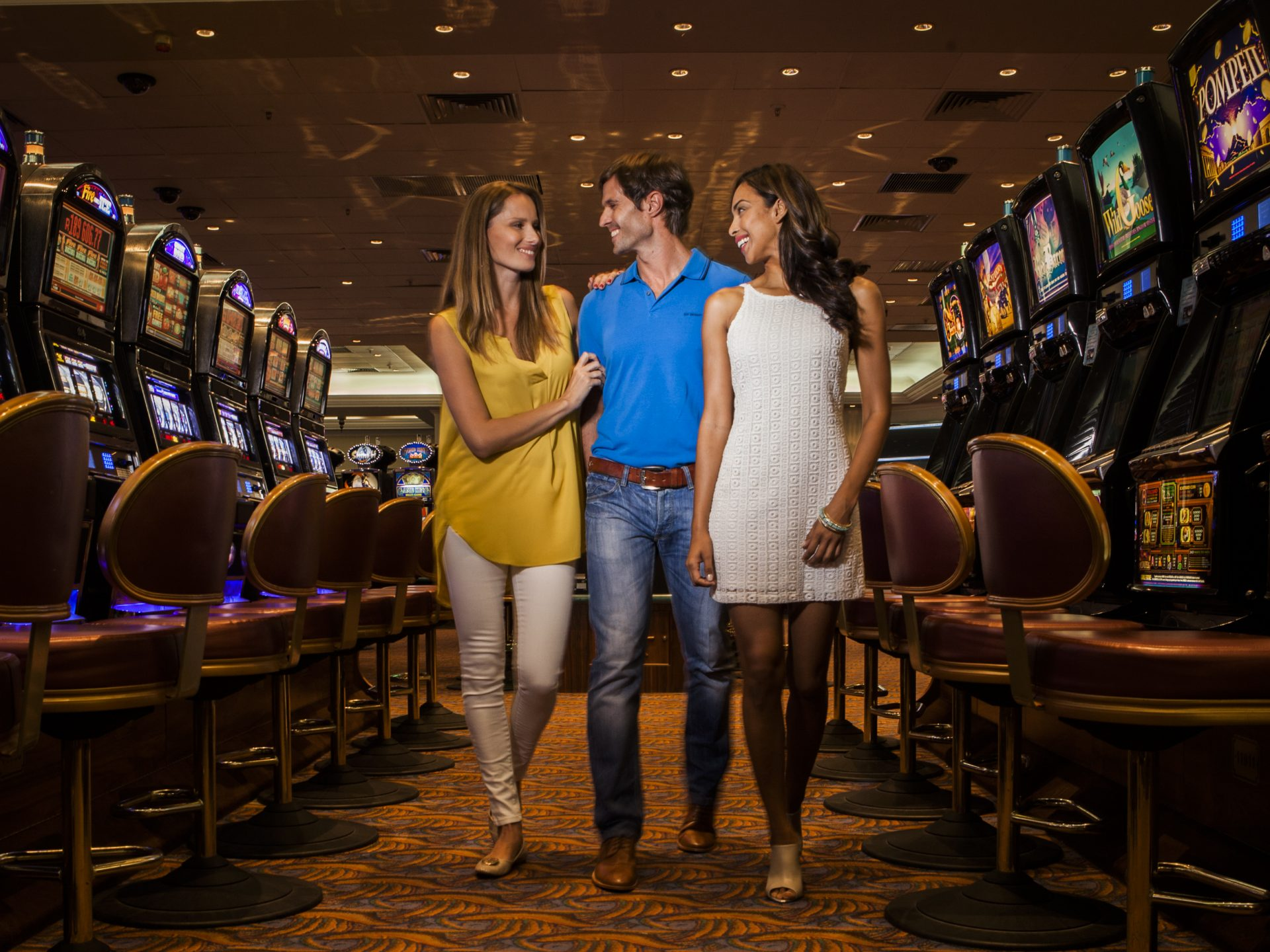 3 People Walking Past The Slot Machines