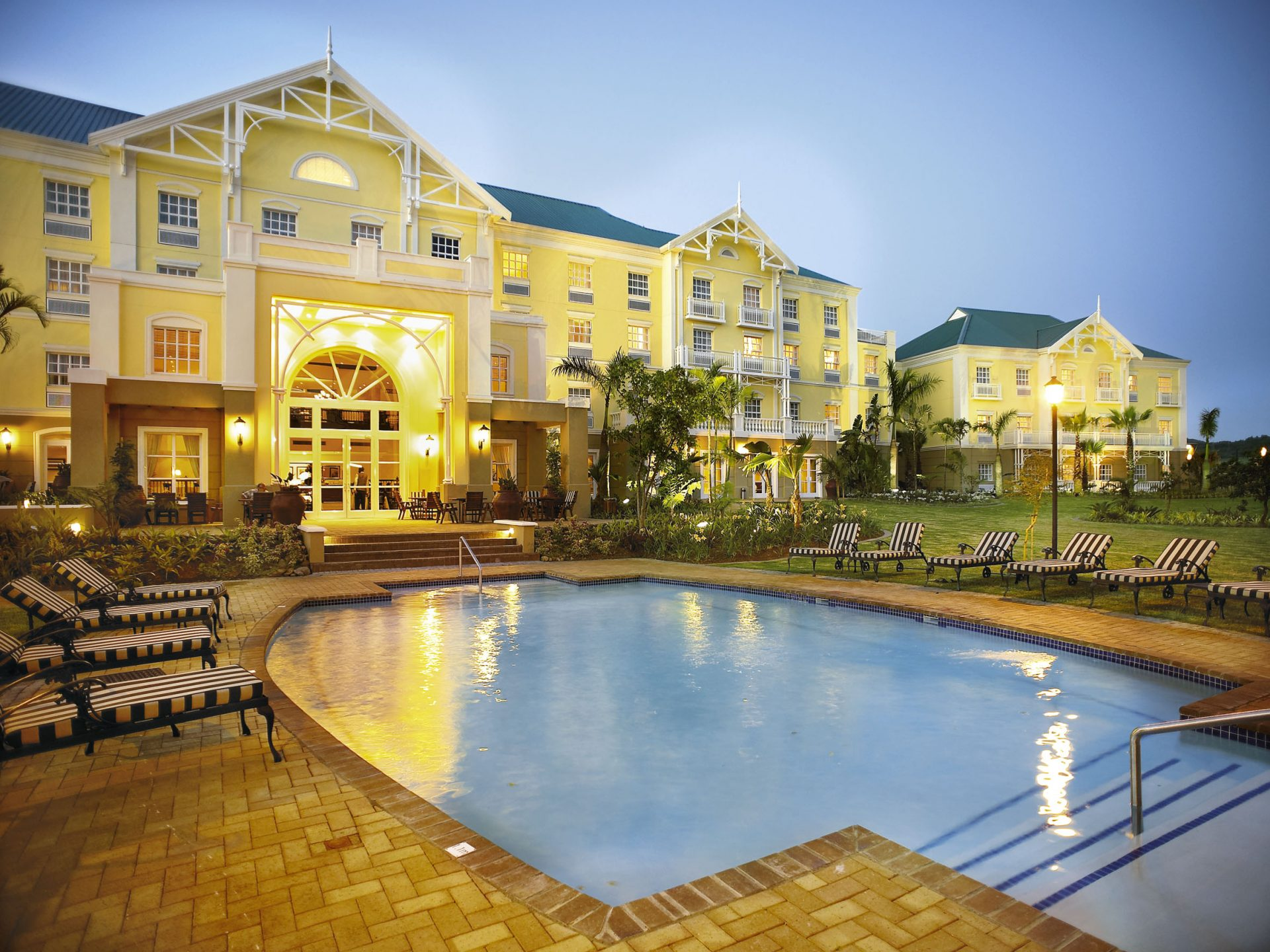 Exterior Of Hotel With Pool Area At Dusk