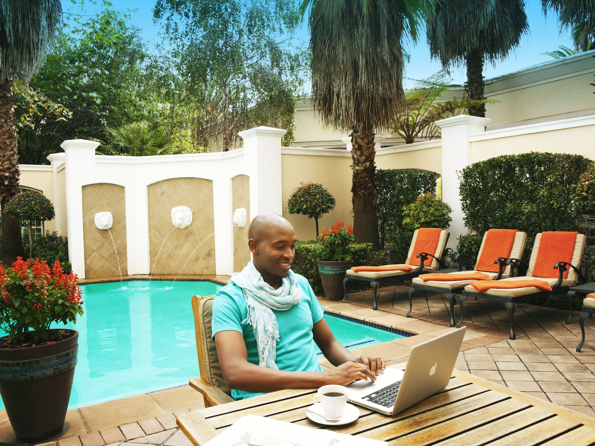 Man at pool side working on laptop
