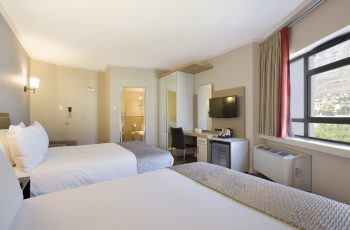 Room with two double beds at SunSquare Cape Town